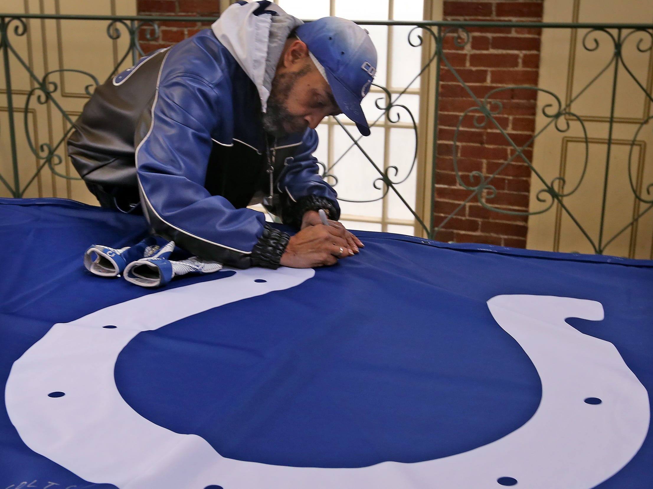 Colts fan David Woods signs a 1-0 banner for the Colts at City Market, Thursday, Jan. 10, 2019.  The banner will be displayed for the team to see at the airport as they head off to their Kansas City playoff game.