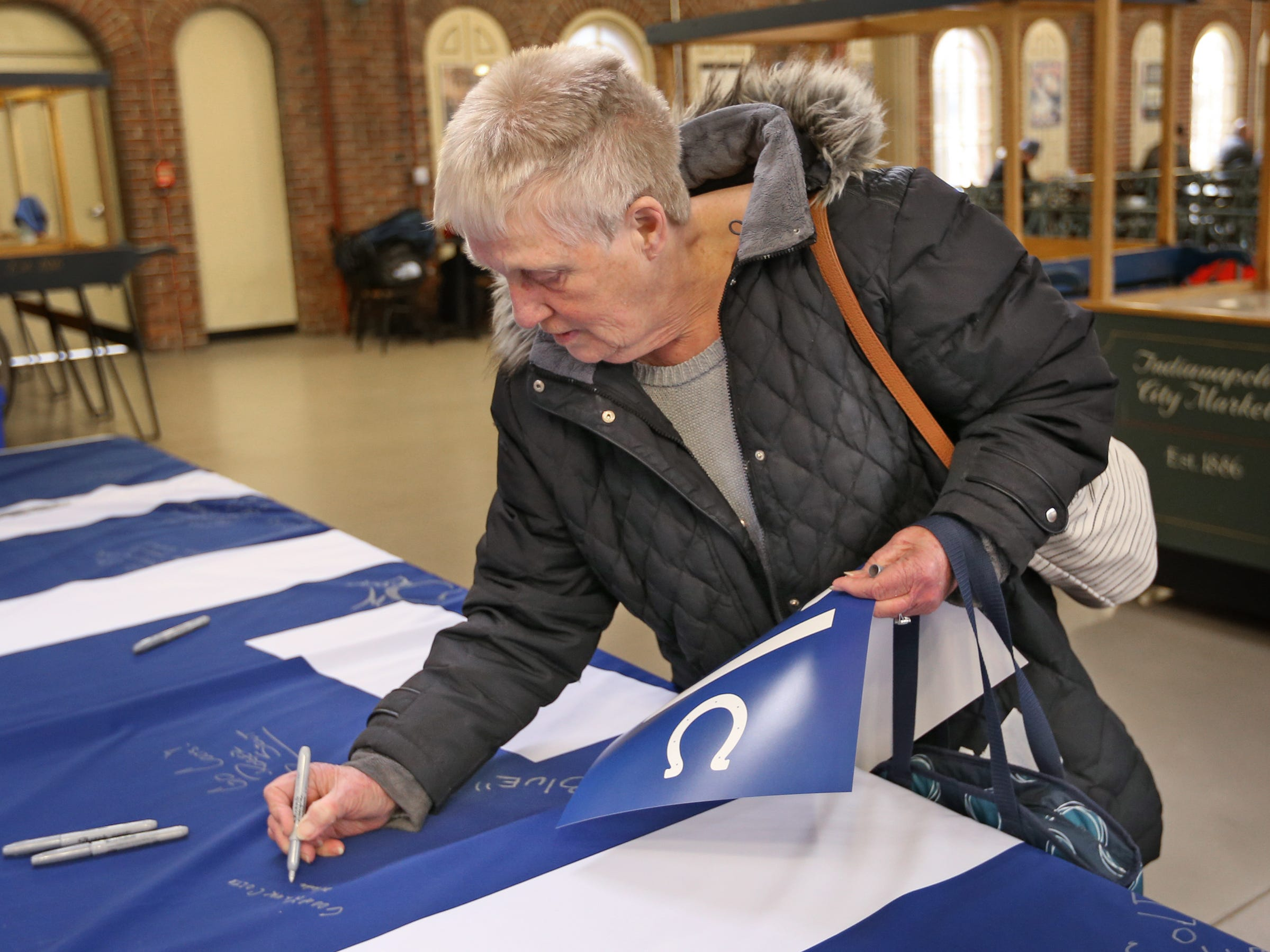 Wanda Pierce joins other fans sign a 1-0 banner for the Colts at City Market, Thursday, Jan. 10, 2019.  The banner will be displayed for the team to see at the airport as they head off to their Kansas City playoff game.