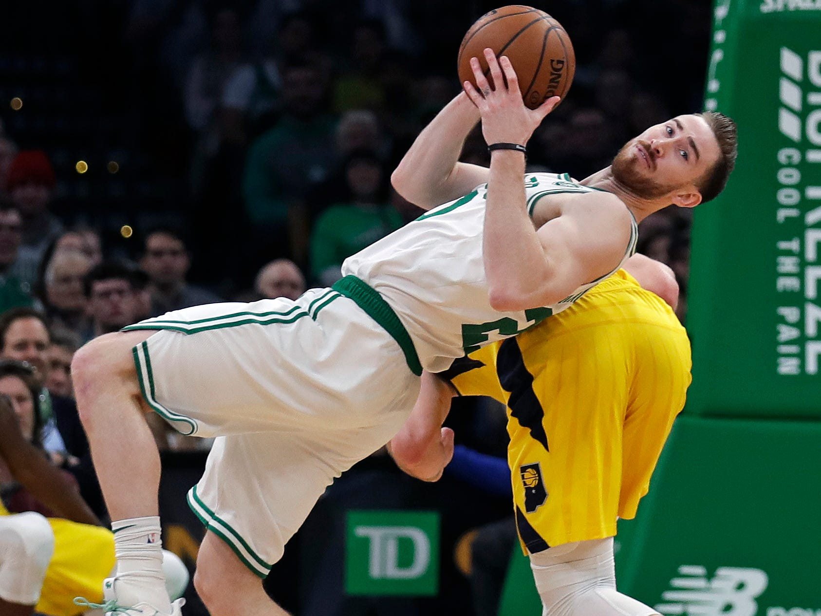 Boston Celtics forward Gordon Hayward, left, looks down court as he grabs a rebound against Indiana Pacers forward Domantas Sabonis, rear, during the first quarter of an NBA basketball game in Boston, Wednesday, Jan. 9, 2019.