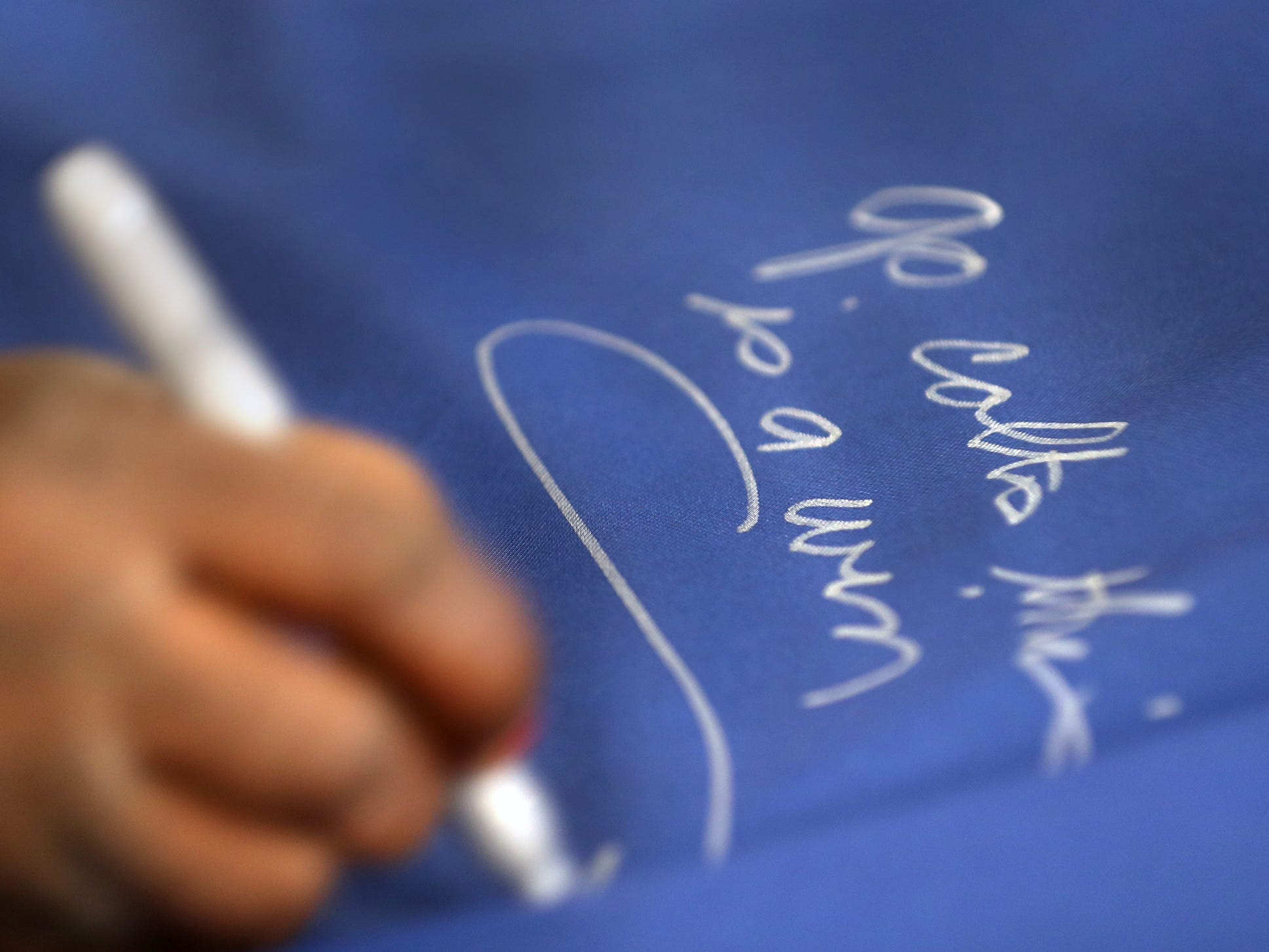 Connie Allender and other fans sign a 1-0 banner for the Colts at City Market, Thursday, Jan. 10, 2019.  The banner will be displayed for the team to see at the airport as they head off to their Kansas City playoff game.