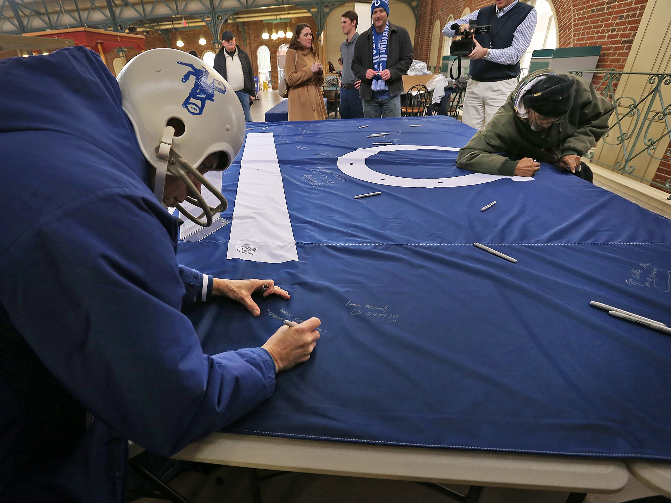Colts fans Paul Diebold, left, and Thomas Bridgeforth sign a 1-0 banner for the Colts at City Market, Thursday, Jan. 10, 2019.  The banner will be displayed for the team to see at the airport as they head off to their Kansas City playoff game.