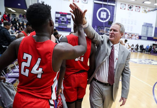 From right, Pike Red Devils head coach Bill Zych congratulates players after they defeated the Ben Davis Giants, 78-67, in Marion County quarterfinals at Ben Davis High School in Indianapolis, Wednesday, Jan. 9, 2019.
