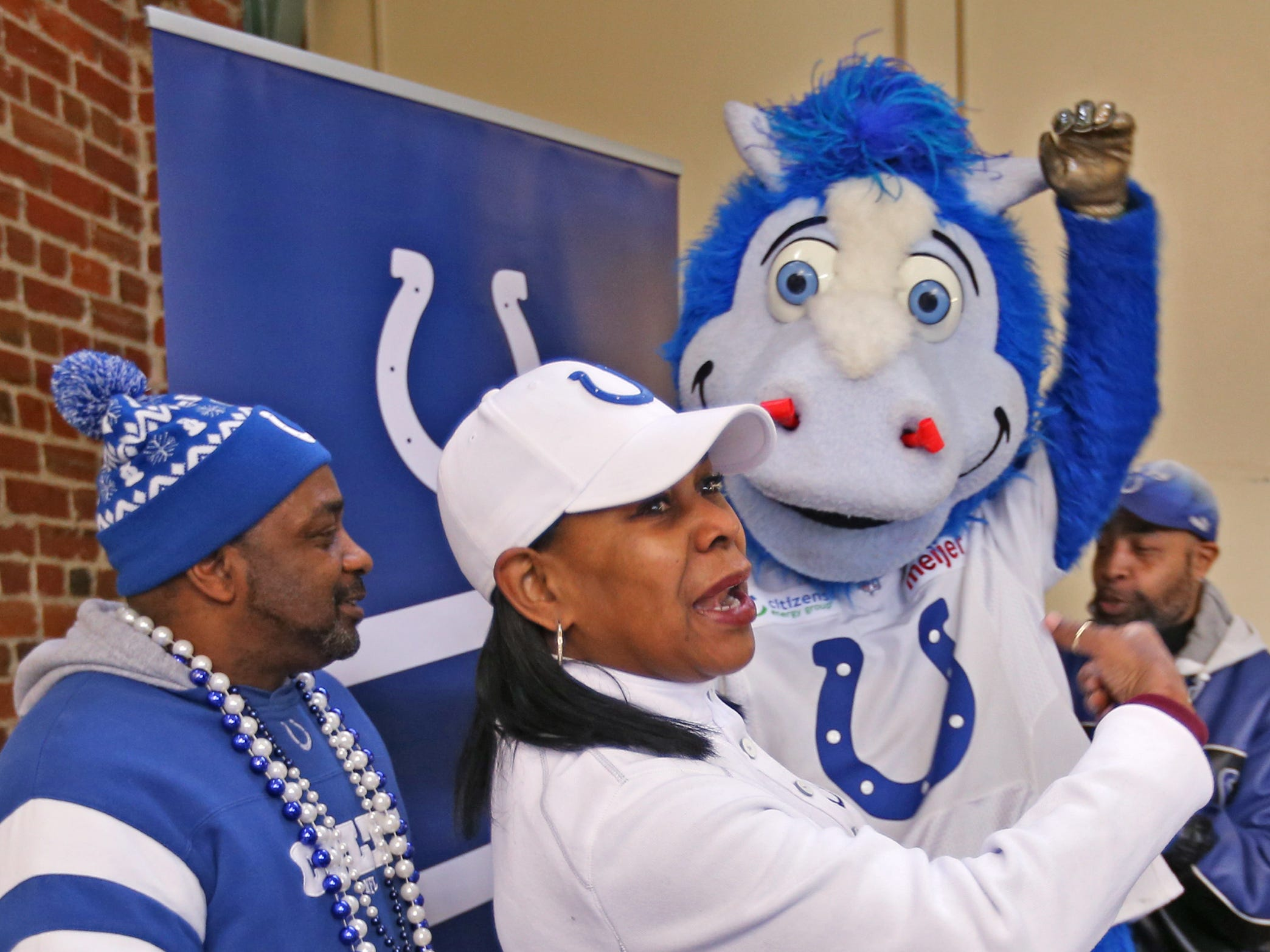 """Colts #1 Fan"" Cheryl McClendon, center, and her ""sidekicks"" George Logan, left, and David Woods laugh with Colts mascot Blue as they pose for photos at the City Market, Thursday, Jan. 10, 2019.  Fans could sign a 1-0 banner in support of the team.  The banner will be displayed for the team to see at the airport as they head off to their Kansas City playoff game."