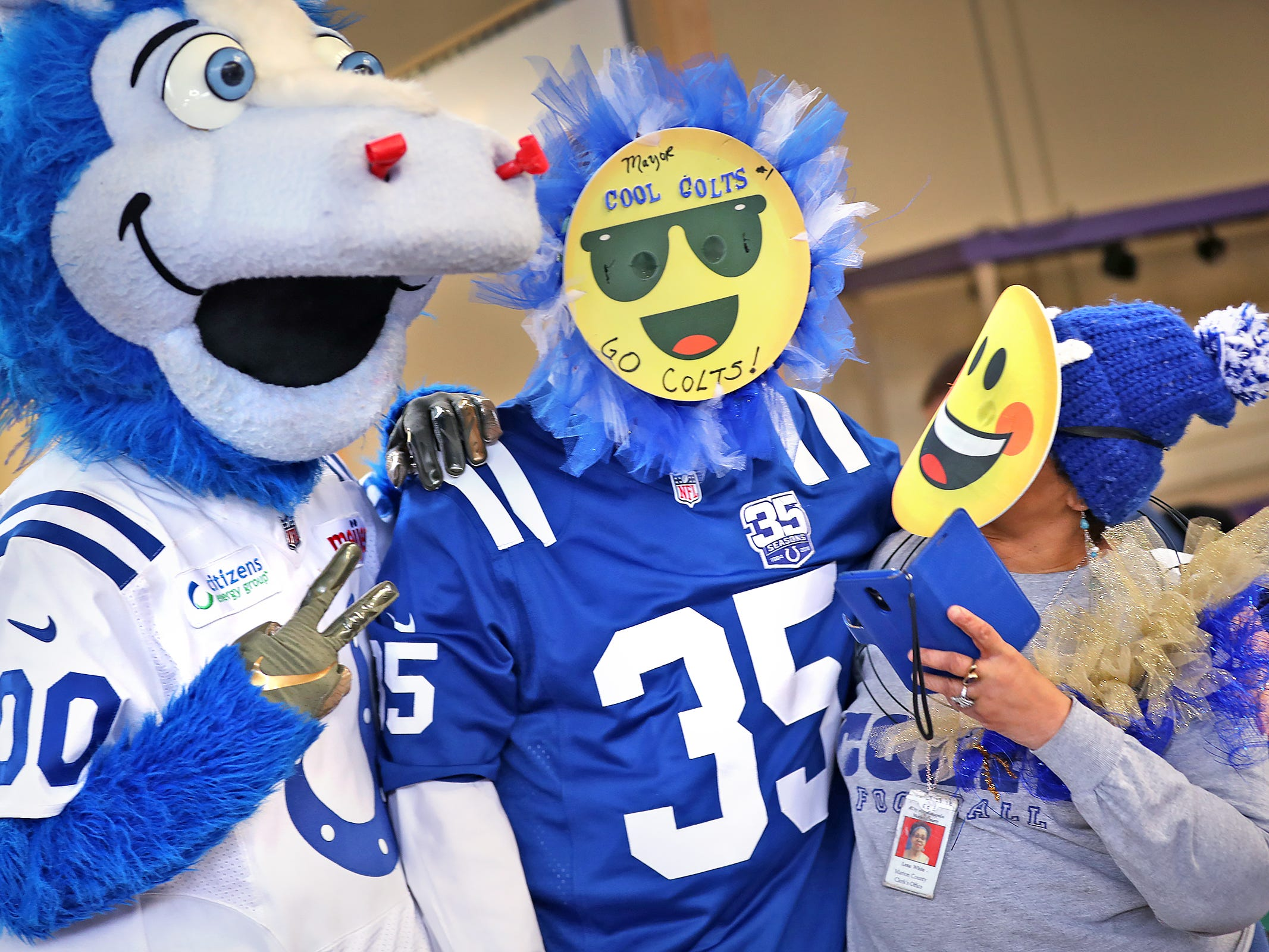 Lonna White, right, gets a hug from Colts mascot Blue, from left, Mayor Joe Hogsett, and Lonna White pose for photos at the City Market.  White makes these fan masks and made the one the mayor is wearing for him.  Fans had the opportunity to sign a 1-0 banner for the Colts at City Market, Thursday, Jan. 10, 2019.  The banner will be displayed for the team to see at the airport as they head off to their Kansas City playoff game.