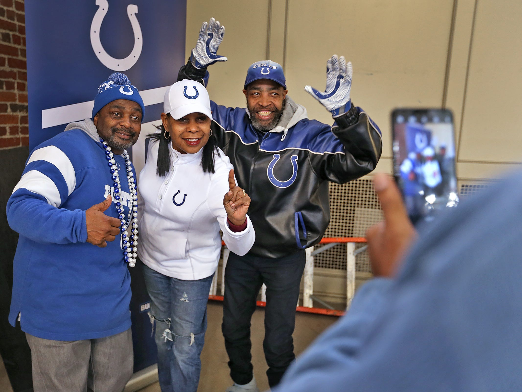 """Colts #1 Fan"" Cheryl McClendon, center, and her ""sidekicks"" George Logan, left, and David Woods pose for photos at the City Market, Thursday, Jan. 10, 2019.  Fans could sign a 1-0 banner in support of the team.  The banner will be displayed for the team to see at the airport as they head off to their Kansas City playoff game."