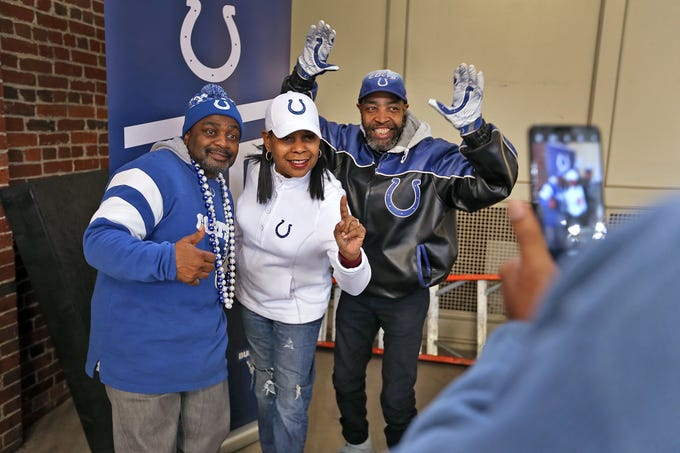 """""""Colts #1 Fan"""" Cheryl McClendon, center, and her """"sidekicks"""" George Logan, left, and David Woods pose for photos at the City Market, Thursday, Jan. 10, 2019.  Fans could sign a 1-0 banner in support of the team.  The banner will be displayed for the team to see at the airport as they head off to their Kansas City playoff game."""