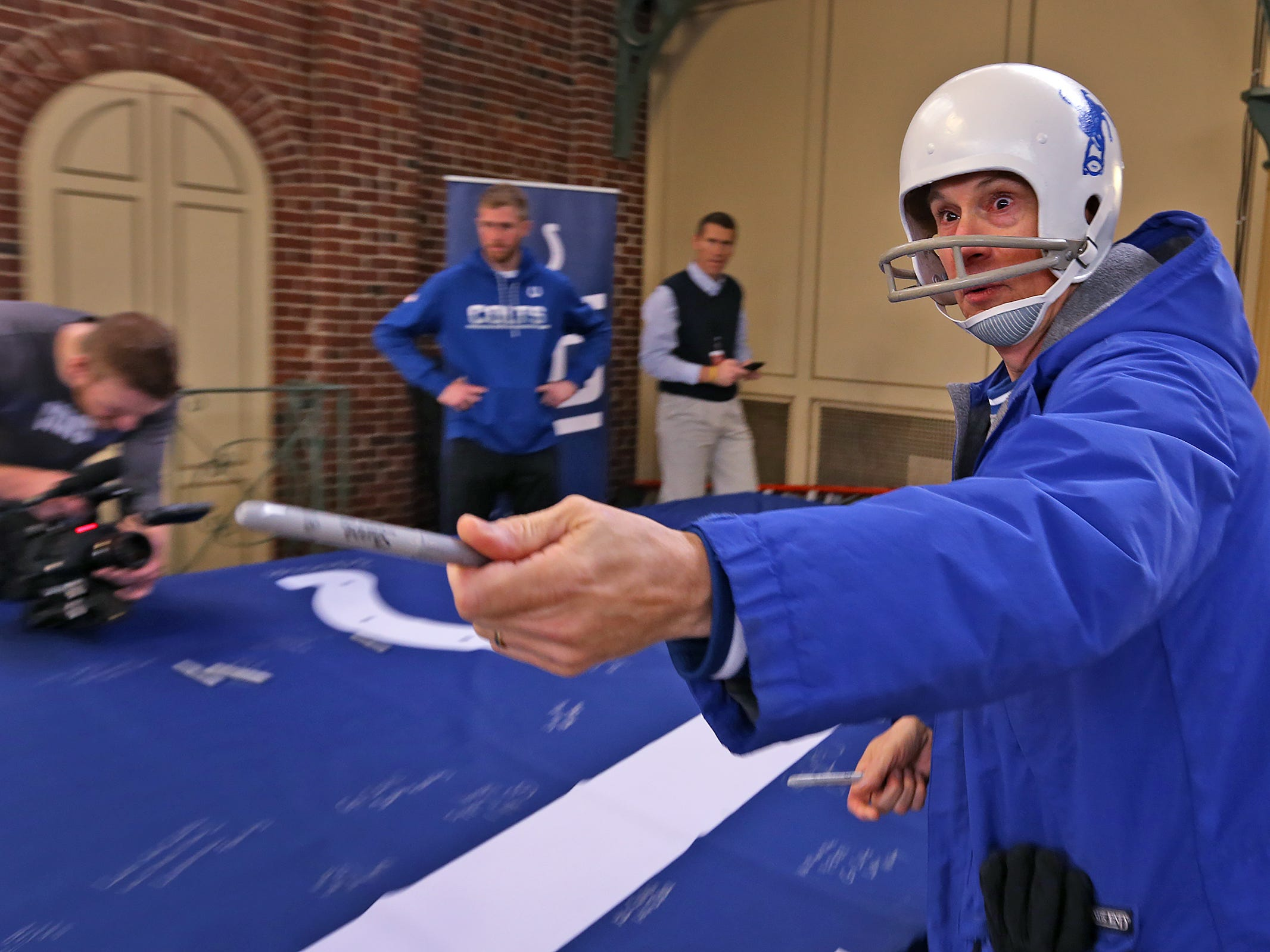 Colts fan Paul Diebold offers someone a pen as fans come together to sign a 1-0 banner for the Colts at City Market, Thursday, Jan. 10, 2019.  The banner will be displayed for the team to see at the airport as they head off to their Kansas City playoff game.