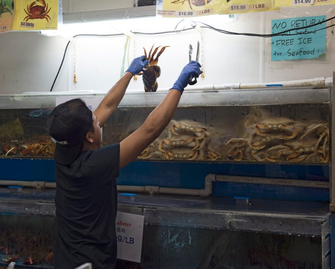An attendant in the seafood market of Mr. Chen's removes a Dungeness crab for a customer. Monday, Jan. 7, 2019.