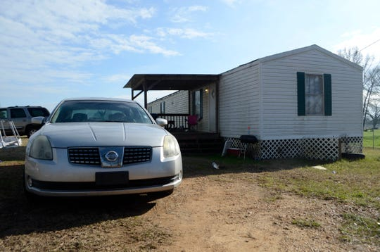 In this Tuesday, Jan. 8, 2019 photo, Ericka Hall's car is parked next to the family's single-wide trailer outside of Magnolia, Miss. Authorities say two sisters are accused of fatally stabbing and shooting their mother Ericka Hall in southwest Mississippi.