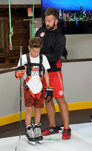 Owner and general manager Bryan Hince shows a student how to use the skating treadmill.