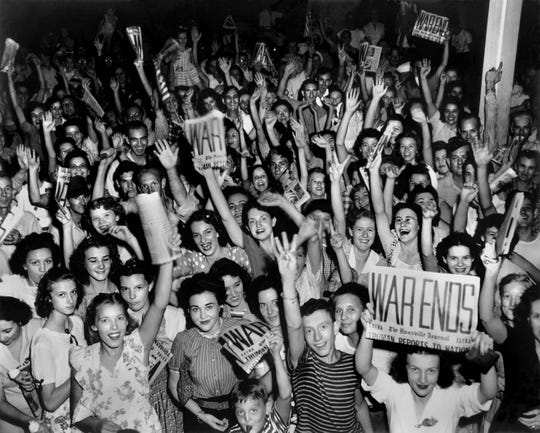 A photograph by Ed Westcott shows Manhattan Project workers celebrating the end of World War II.