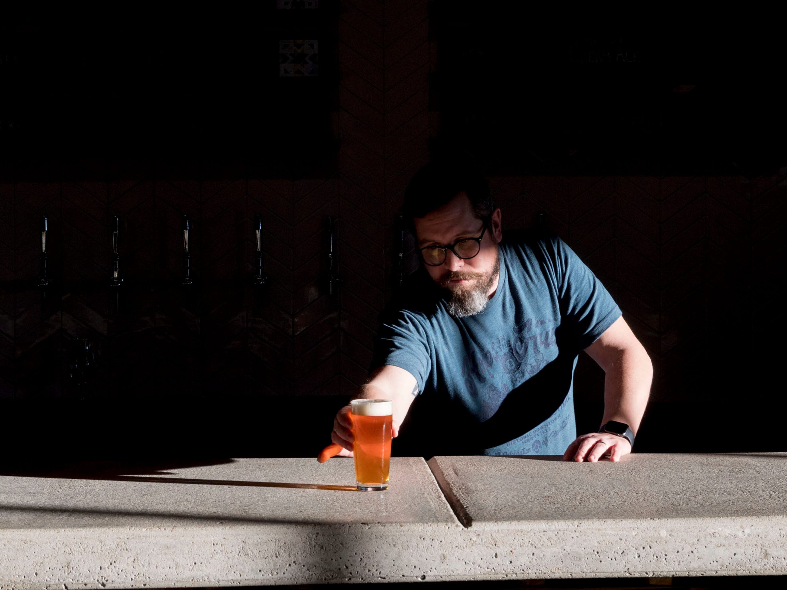 Blackberry Farm Brewery manager Andrew Noye serves a pint of the Brewery's English Pale Ale.