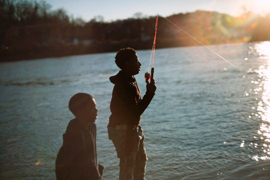 Kyriek George and his cousin Vákarus Bomar, 8, fish from the Riverside Landing boat dock in Knoxville, Tennessee on Wednesday, January 9, 2019, during an unseasonably warm spell earlier this winter.