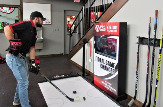 """Demonstrated by Bryan Hince, a state-of-the-art stick station gives real time results and improves stick handling. """"Keep your head up,"""" advises Hince."""