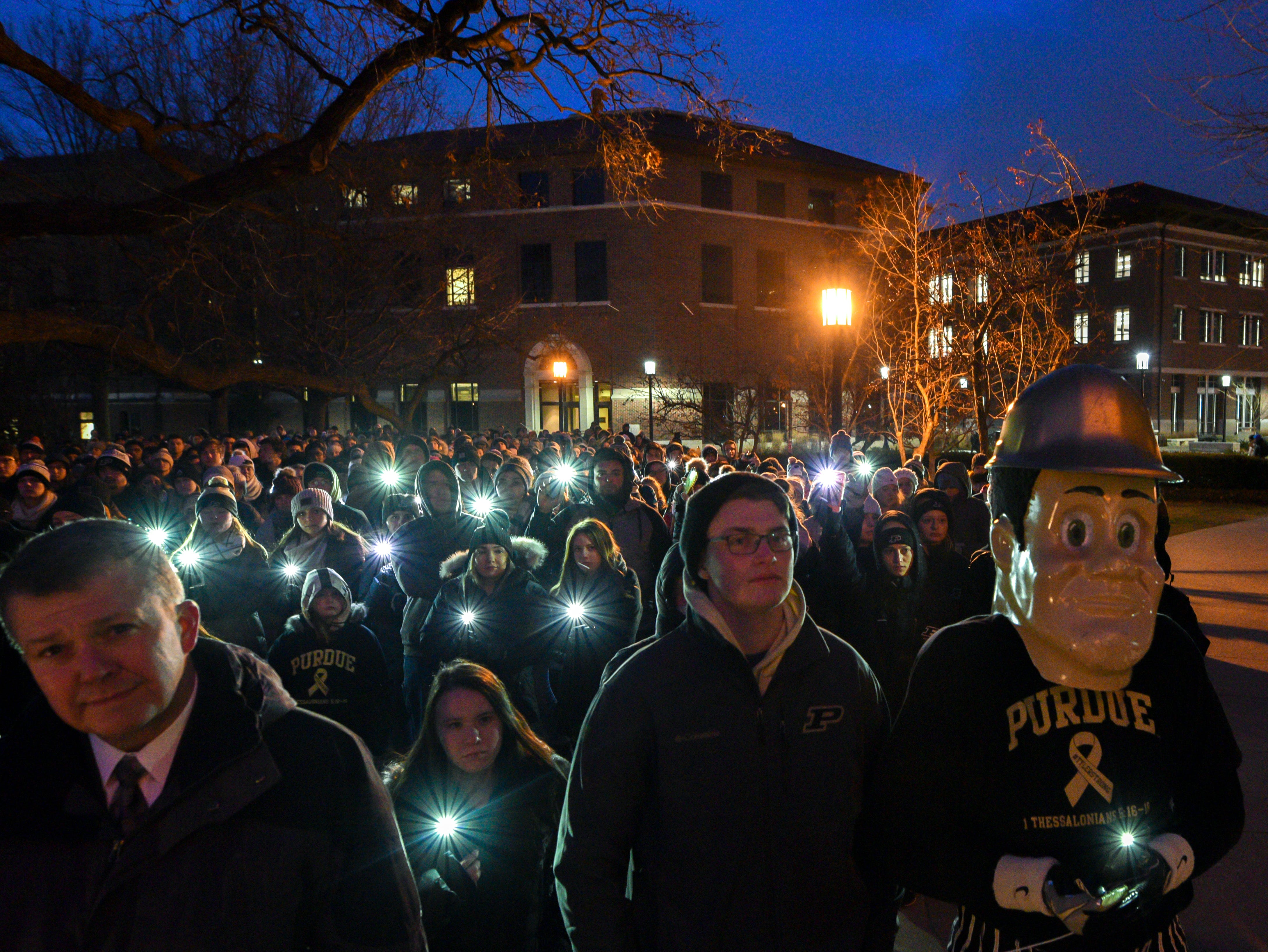 With the wind preventing most candles from staying lighted people used cell phone flashlights at a memorial service and candlelight vigil for Tyler Trent at Purdue University in West Lafayette on January 9, 2019.