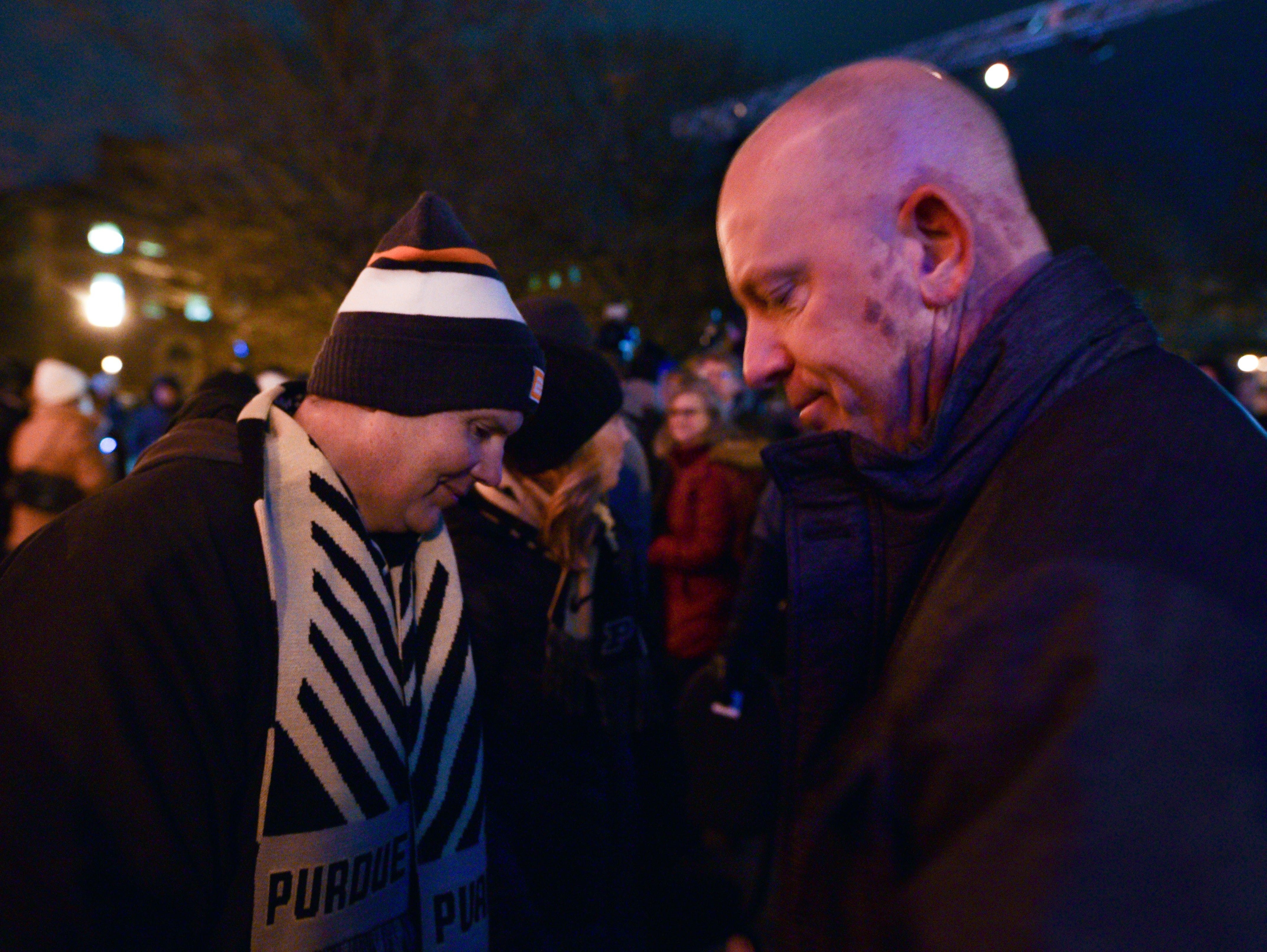 Tony Trent, left, and Purdue football coach Jeff Brohm exchange solemn words at a memorial service and candlelight vigil for Tyler Trent at Purdue University in West Lafayette on January 9, 2019.