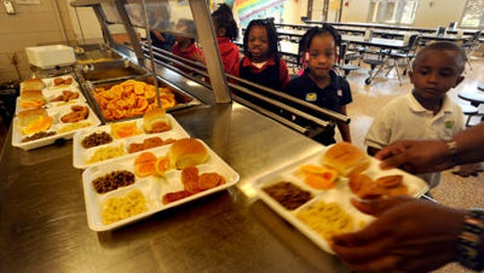 Elementary students line up to eat lunch. Federal dollars are used to pay for many school meals, so officials are monitoring the federal government shutdown for possible future impacts.