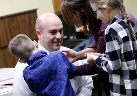 Greenfield Township Fire Chief Brad Smith kneels down as his son Jansen Smith, 7, left, wife Keeley Smith, second from right, and daughter Macey Smith, 10, pin his new rank insignia on his uniform shirt Wednesday night, Jan. 9, 2019, in Greenfield Township. Smith took over as chief of the department on December 30 and was formally sworn in before Wednesday's township trustee meeting. Also sworn in were Capt. Cory Spires, Lt. Carlton Reaves and firefighter Colin Osterman.