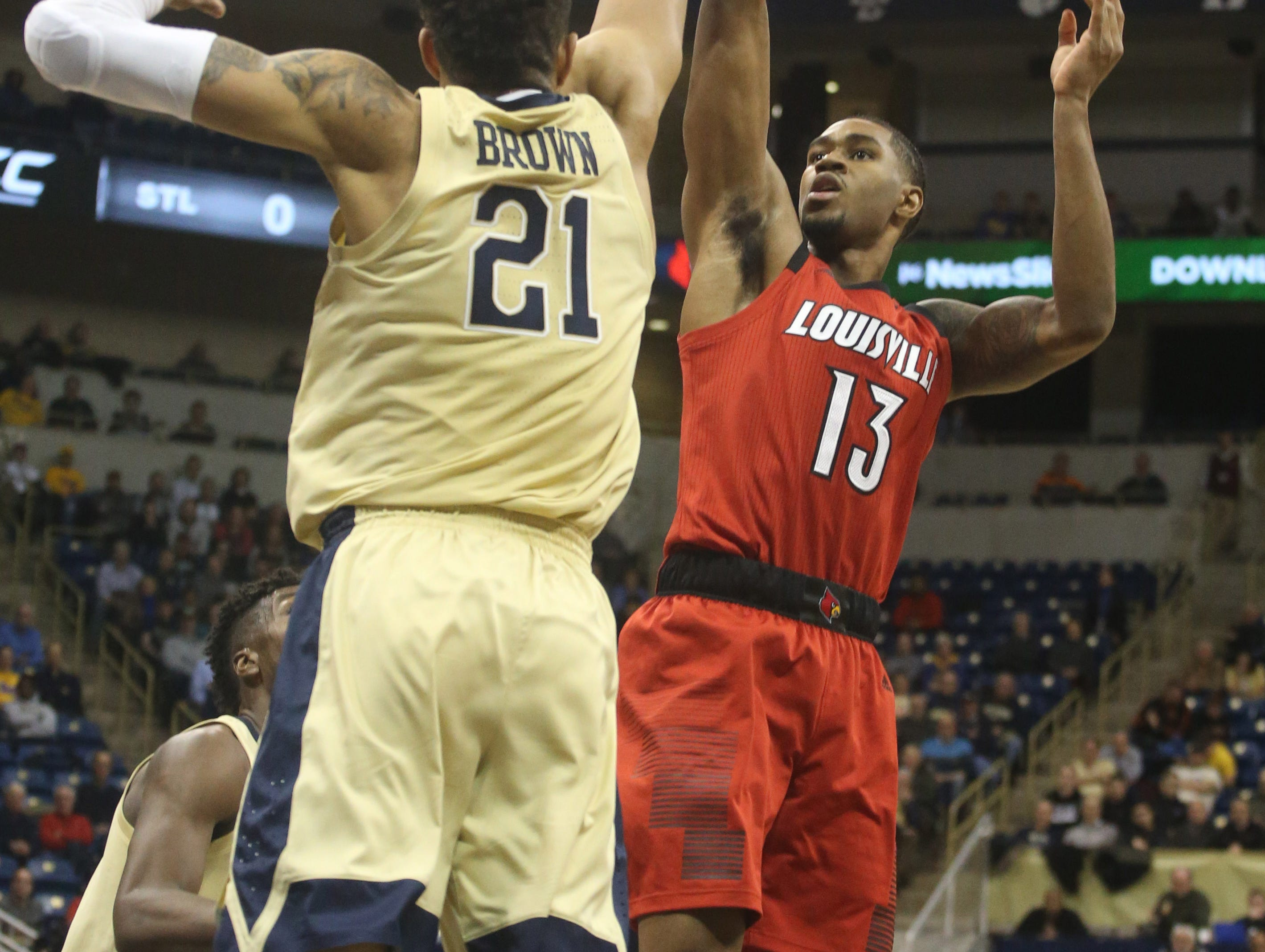 Jan 9, 2019; Pittsburgh, PA, USA;  Louisville Cardinals forward V.J. King (13) shoots over Pittsburgh Panthers forward Terrell Brown (21) during the first half at the Petersen Events Center.
