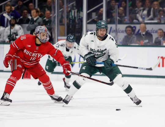 Michigan State's Patrick Khodorenko, right, controls the puck against Ohio State's Quinn Preston during an NCAA hockey game on Saturday, Jan. 5, 2019, in East Lansing, Mich.