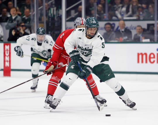 Michigan State's Patrick Khodorenko controls the puck against Ohio State's Quinn Preston, rear, during an NCAA hockey game on Saturday, Jan. 5, 2019, in East Lansing, Mich.