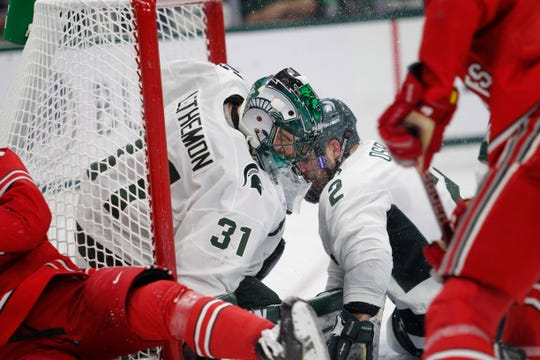 Michigan State goalkeeper John Lethemon (31) and defenseman Zach Osburn (2) make a stop against Ohio State during an NCAA hockey game on Saturday, Jan. 5, 2019, in East Lansing, Mich.