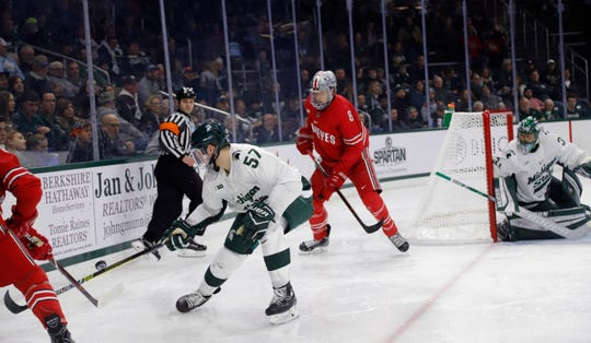 Michigan State's Jerad Rosburg (57) controls the puck against Ohio State's Dakota Joshua (8) as Michigan State goalkeeper John Lethemon, right, watches during an NCAA hockey game on Saturday, Jan. 5, 2019, in East Lansing, Mich.