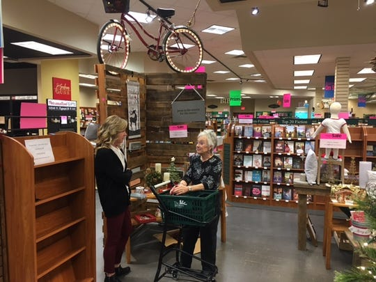 Tammie Owens, at left, manager of The Bookery, talks with a customer Thursday. The store is closing Feb. 23 as owner Mark Stofer is retiring.
