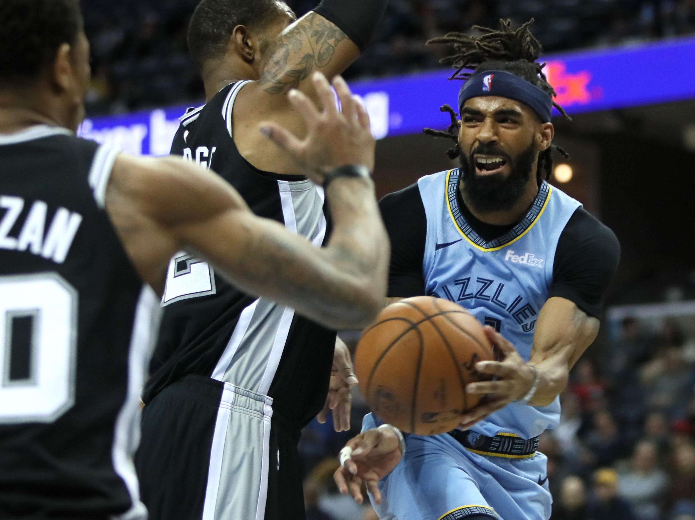 Memphis Grizzlies guard Mike Conley passes the ball past San Antonio Spurs defender LaMarcus Aldridge during their game at the FedExForum on Wednesday, Jan. 9, 2019.