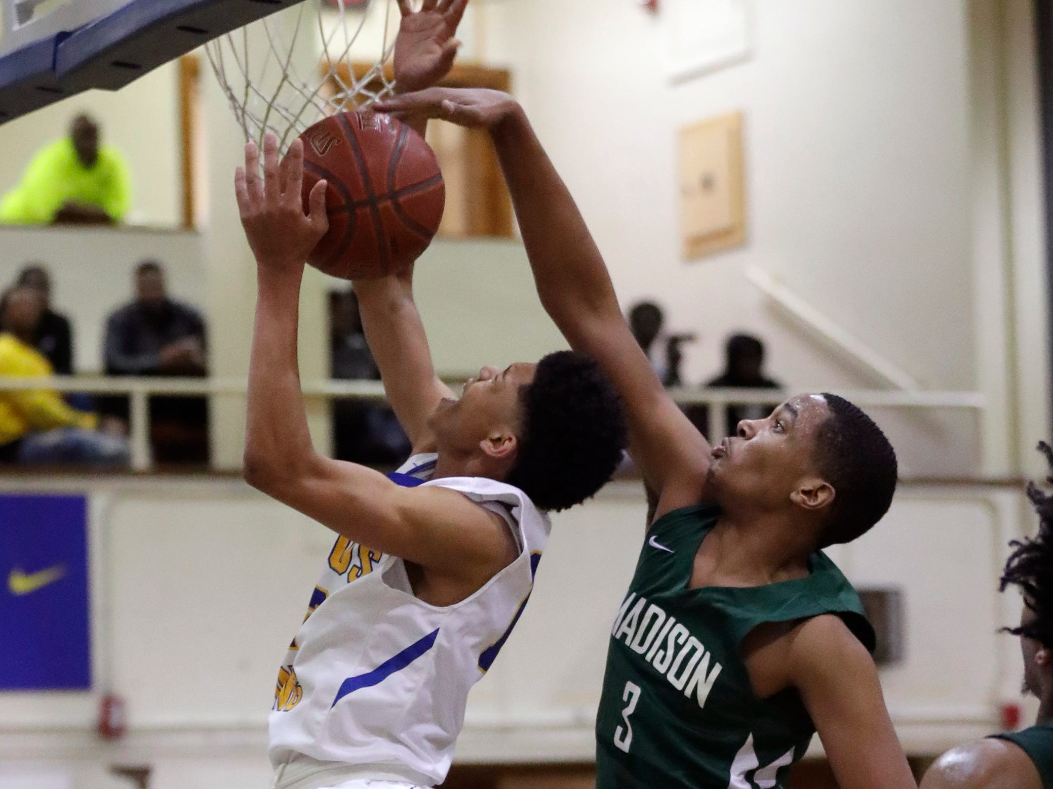 Milwaukee Madison's Davin Johnson blocks the shot of Milwaukee King's  Quinton Murrell on Wednesday, Jan. 9, during a key City Conference game at Rufus King High School.