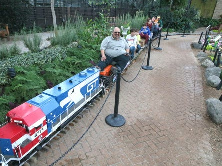 The Milwaukee Light Engineering Society set up a hundred feet of track on the walkway in the Show Dome to give rides to event-goers at the 2018 train show.   Engineer Bob Gallegos sits behind the GP38 locomotive to give the rides.