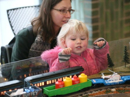 Norah Ballweg age 2 of Waukesha and her mother Betty Ballweg (rear) look over the Lionel Railroad Club of Milwaukee's train layout at the 2018 train show.
