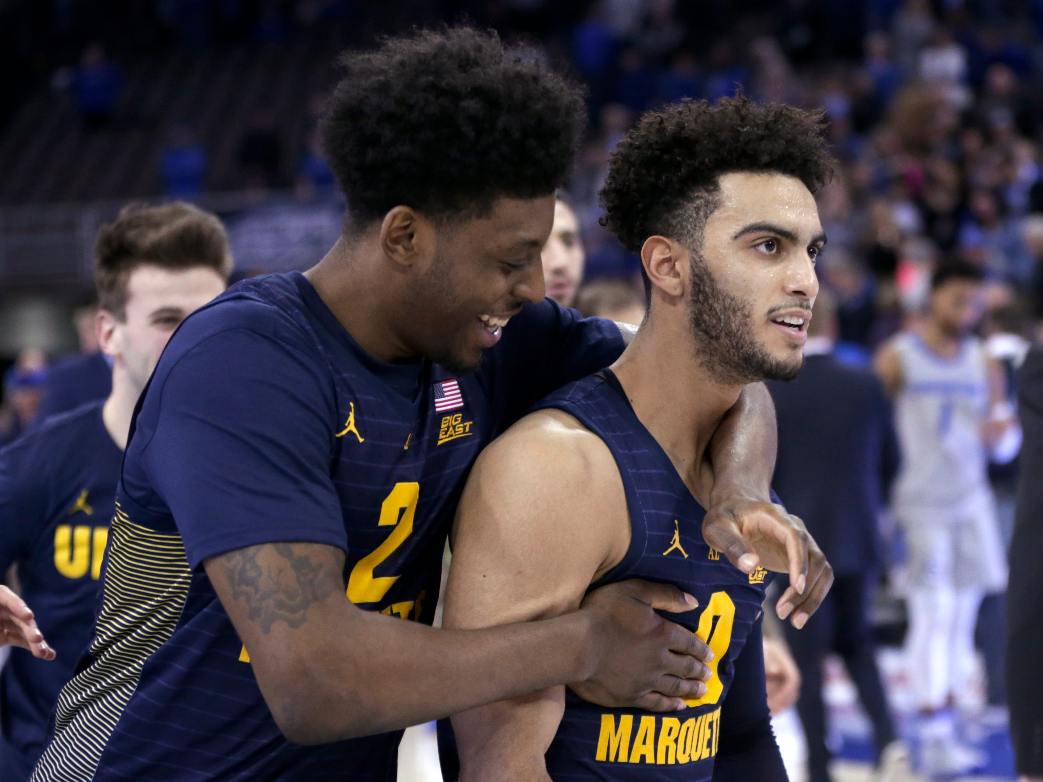 Sacar Anim (left) and Markus Howard celebrate after Marquette's 106-104 overtime victory over Creighton on Wednesday night.
