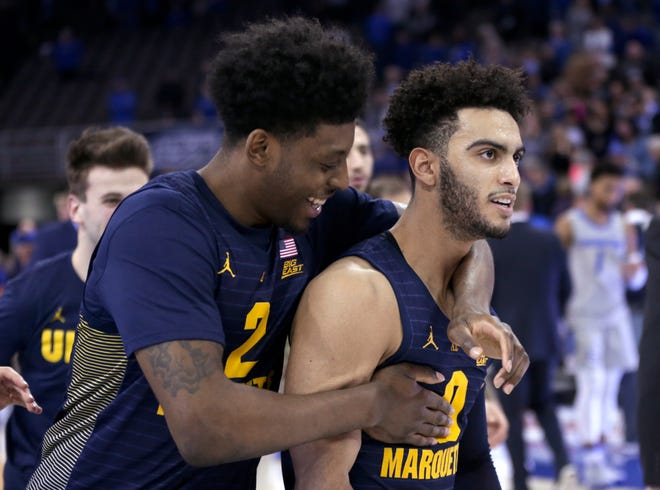 Sacar Anim (left) and Markus Howard celebrate after Marquette's 106-104 overtime victory over Creighton on Wednesday night. Howard finished with a school- and Big East-record 53 points against the Bluejays.