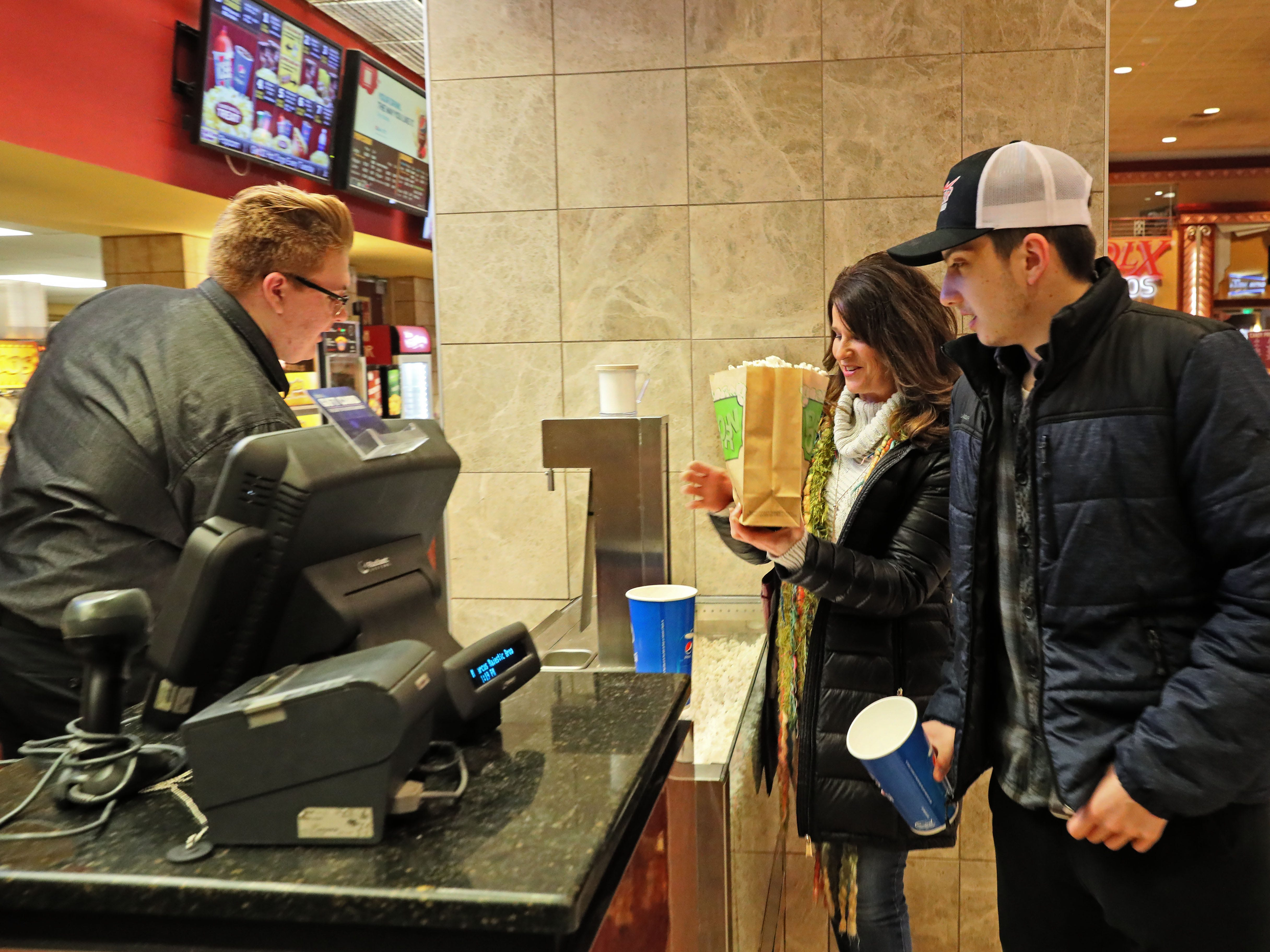 Lisa Daury of Hartland and her son Jon Daury, who is home on break from the University of Wisconsin-Madison, get some popcorn before their movie from Jordyn Kowalke at the Marcus Majestic Cinema, 770 Springdale Road in Brookfield.