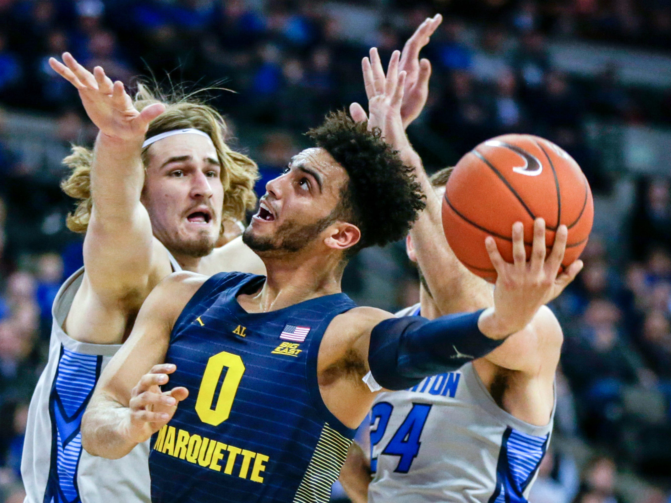Marquette's Markus Howard goes to the basket in front of Creighton's SamsonFroling during the first half Wednesday night.