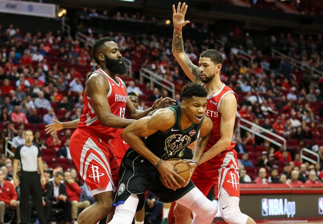 Giannis Antetokounmpo sneaks between Rockets guards James Harden and Austin Rivers
