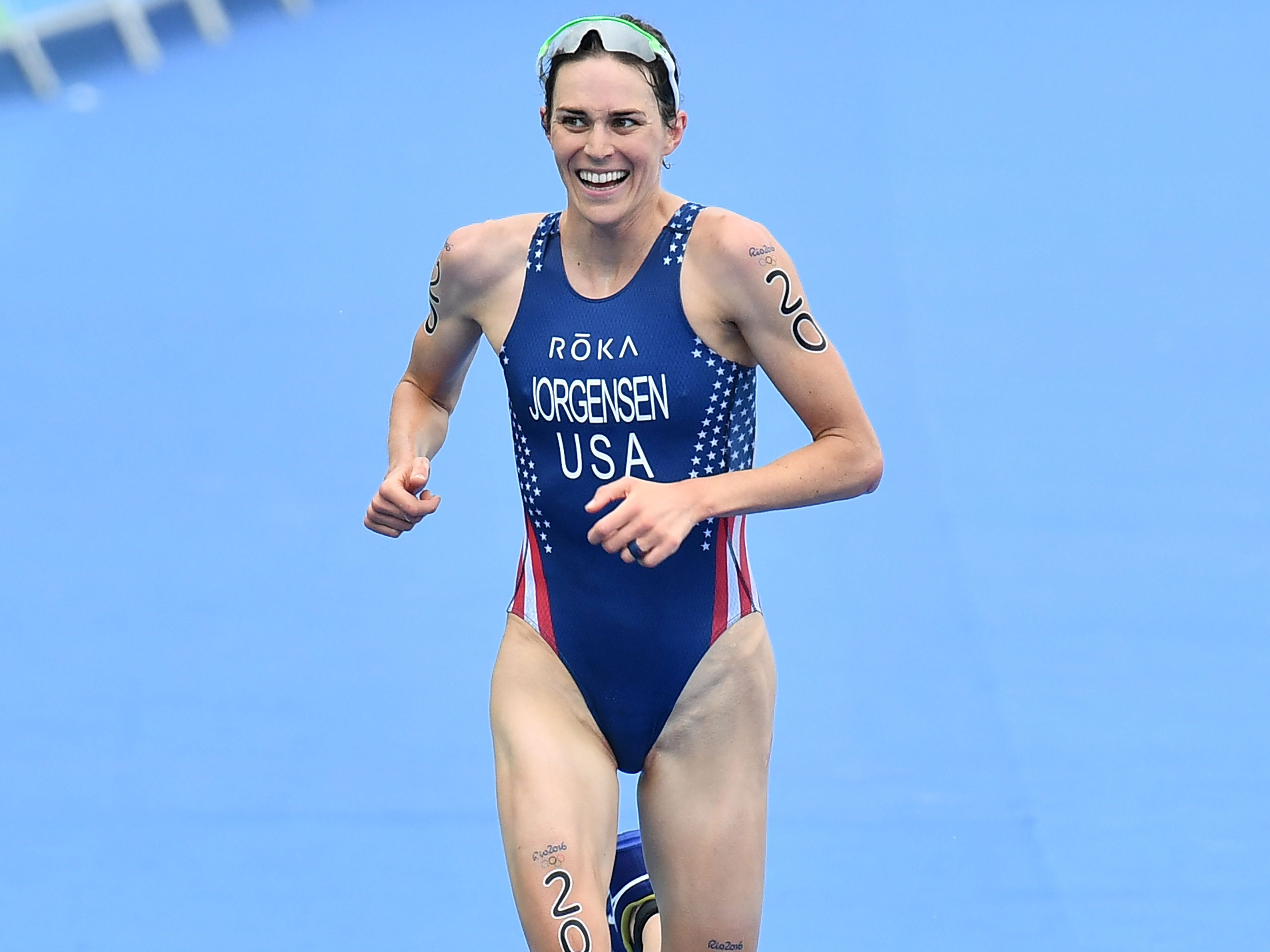 USA's Gwen Jorgensen runs to the finish line to win the gold medal in the women's triathlon at Fort Copacabana during the Rio 2016 Olympic Games in Rio de Janeiro on August 20, 2016. / AFP PHOTO / Leon NEALLEON NEAL/AFP/Getty Images