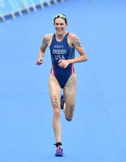 USA's Gwen Jorgensen runs to the finish line to win the gold medal in the women's triathlon at Fort Copacabana during the Rio 2016 Olympic Games in Rio de Janeiro on August 20, 2016