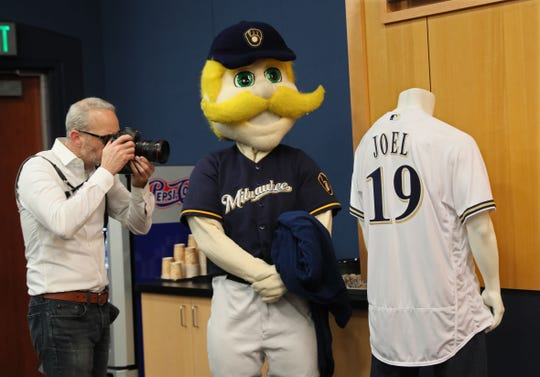 Milwaukee Brewers photographer Scott Paulus photographs the team jersey that Bernie Brewer unveiled at a news conference to announce a Billy Joel concert coming to Miller Park April 26.