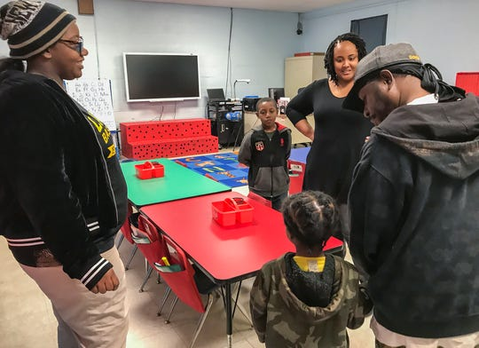 Kindergarten teacher Tanika Yanez (center back) talks to Johntavian Jackson and his family about her new classroom at Morehouse Junior High School on Wednesday. Jackson will be in the same table,  with the same chair and same classmates and teacher as when he attended the now-closed H.V. Adams Elementary.