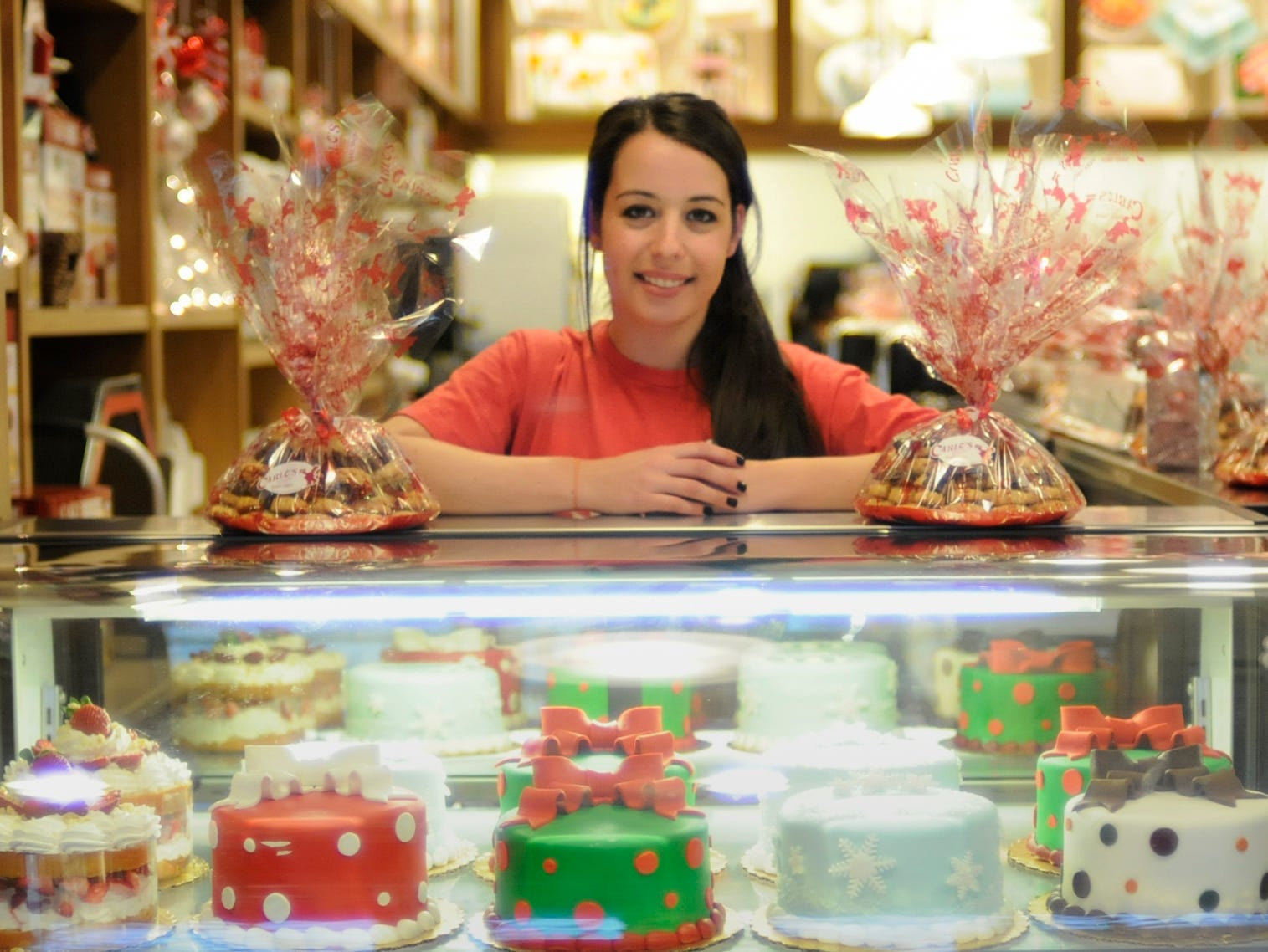 Carlo's Bakery Ridgewood General Manager, Marissa Lopez, among colorful cakes and pastries after the opening in December 2013.
