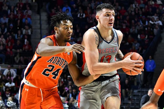 Jan 9, 2019; Oxford, MS, USA; Mississippi Rebels center Dominik Olejniczak (13) handles the ball while being defended by Auburn Tigers forward Anfernee McLemore (24) during the second half at The Pavilion at Ole Miss. Mandatory Credit: Matt Bush-USA TODAY Sports