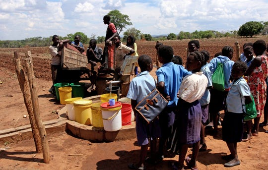 Students from Chizukwe primary school in Zambia gather water from a well that was funded by a school in Alabama.