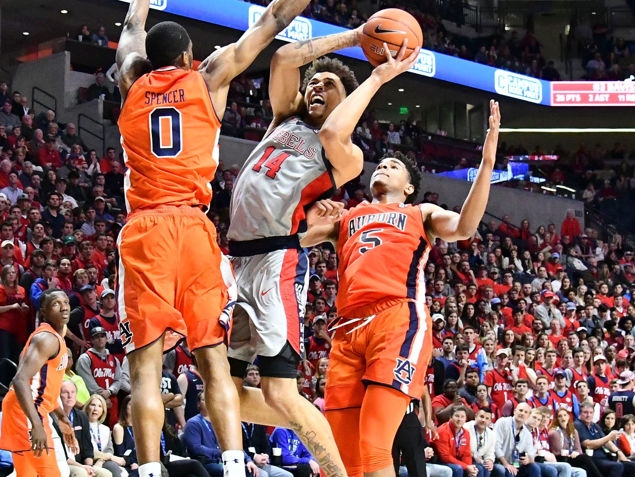 Jan 9, 2019; Oxford, MS, USA; Mississippi Rebels forward KJ Buffen (14) goes up for a shot defended by Auburn Tigers forward Horace Spencer (0) and forward Chuma Okeke (5) during the second half at The Pavilion at Ole Miss. Mandatory Credit: Matt Bush-USA TODAY Sports