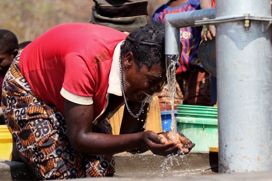 A woman washes in a newly installed well in Kaole Village in Zambia.