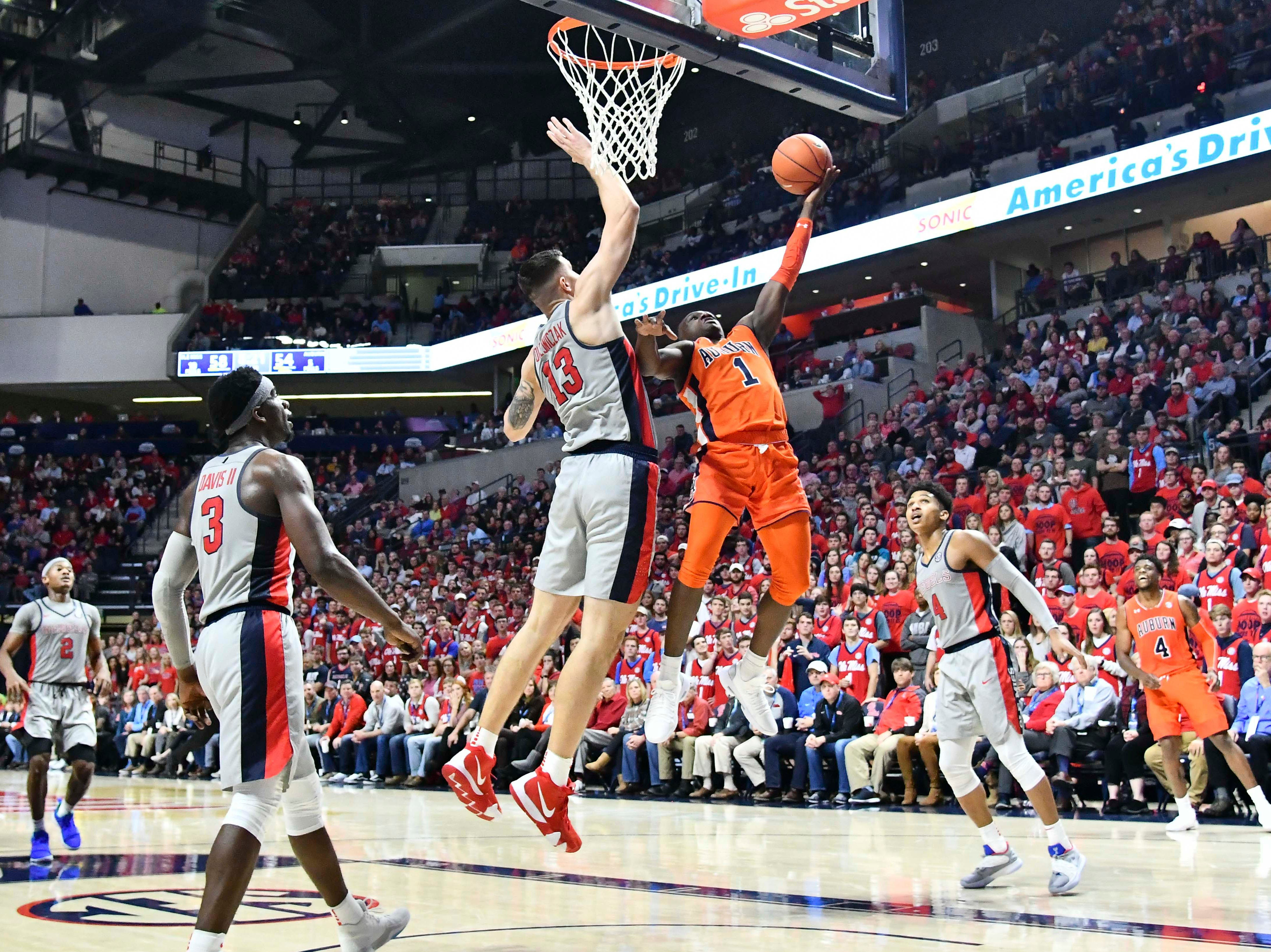 Jan 9, 2019; Oxford, MS, USA; Auburn Tigers guard Jared Harper (1) goes up for a shot against Mississippi Rebels center Dominik Olejniczak (13) during the second half at The Pavilion at Ole Miss. Mandatory Credit: Matt Bush-USA TODAY Sports