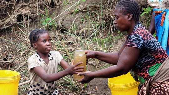 A woman hands drinking water to a child in a Zambian village that doesn't have access to clean water.