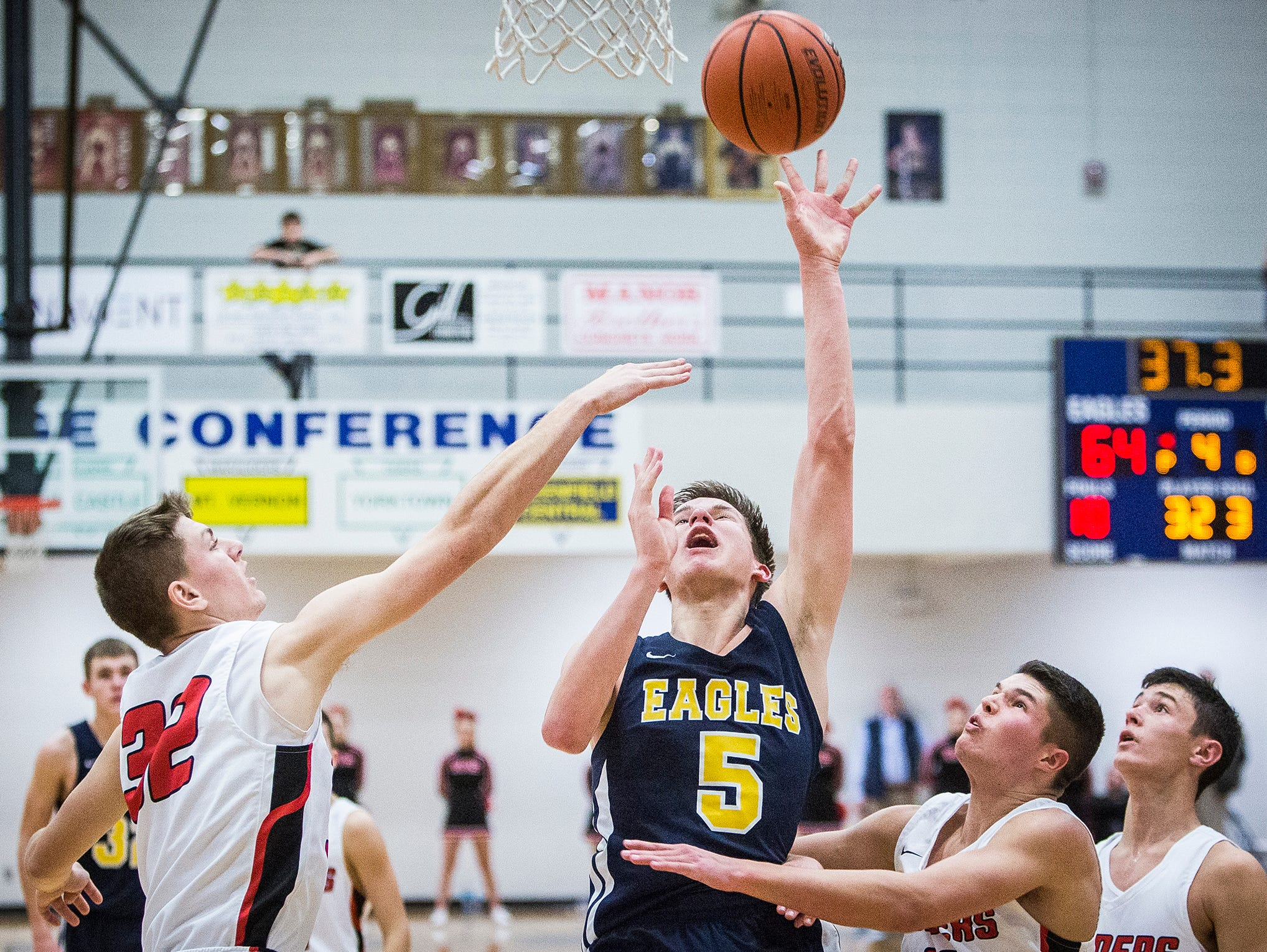 Delta's Josh Bryan shoots past Wapahani's defense during the Delaware County Basketball Tournament at Delta High School Tuesday, Jan. 8, 2019.