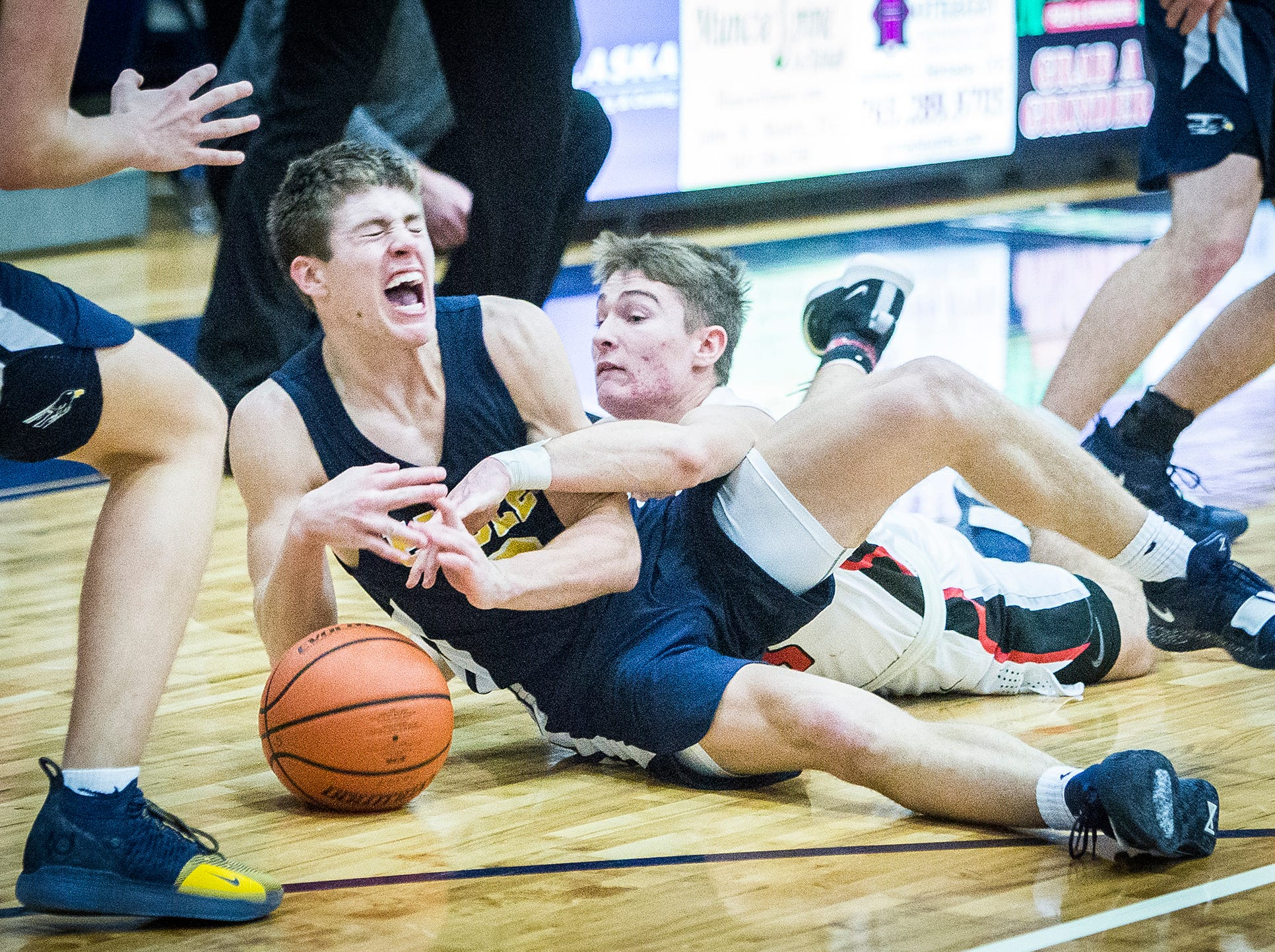 Delta's Zach Garner fights for possession against Wapahani's Garett Stanley during the Delaware County Basketball Tournament at Delta High School Tuesday, Jan. 8, 2019.